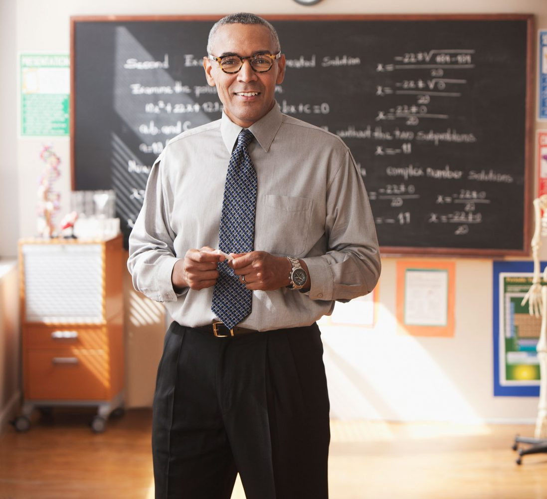 A teacher in a classroom with a blackboard behind him.