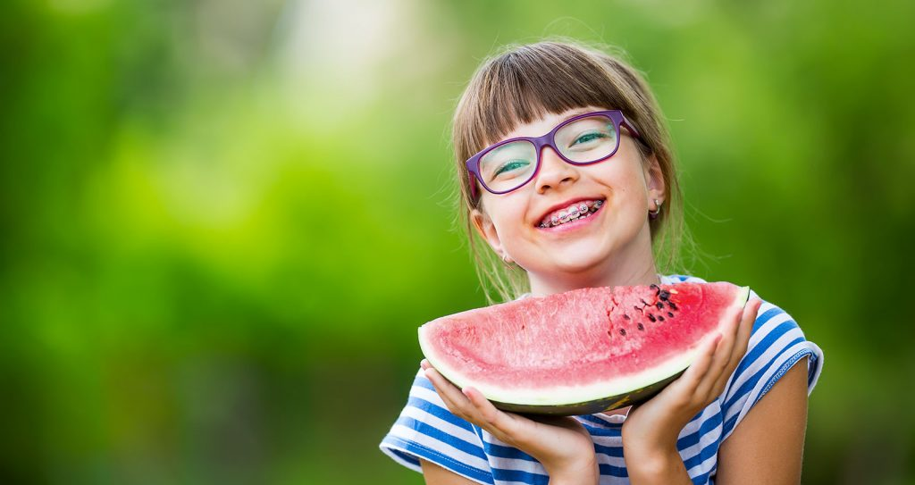 Young girl with glasses eating watermelon.