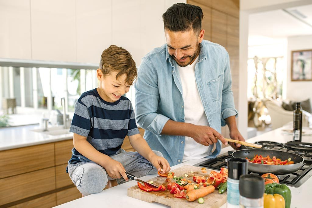 Father and child cutting veggies