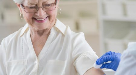 Nurse swabs arm of woman for vaccination
