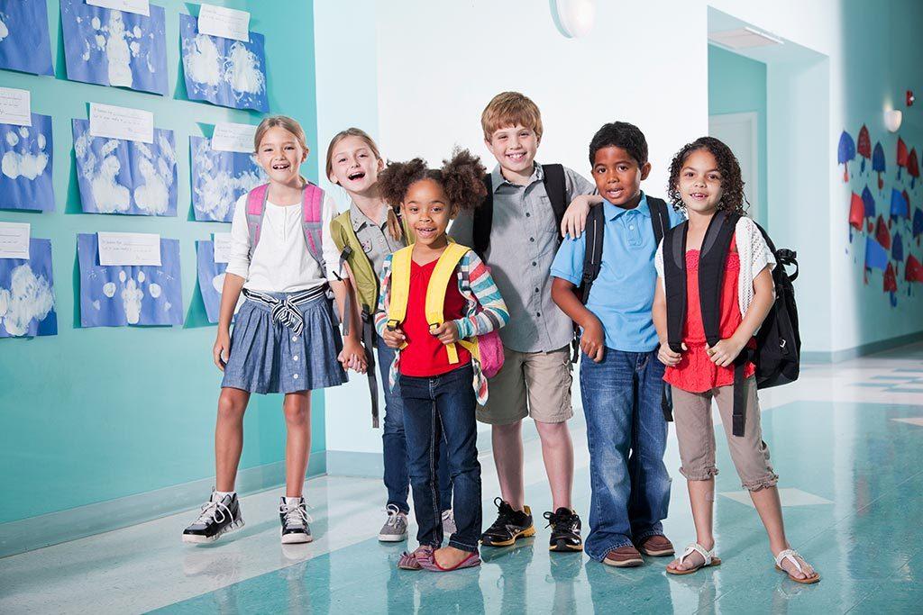 A groupd of children standing in a school hallway.