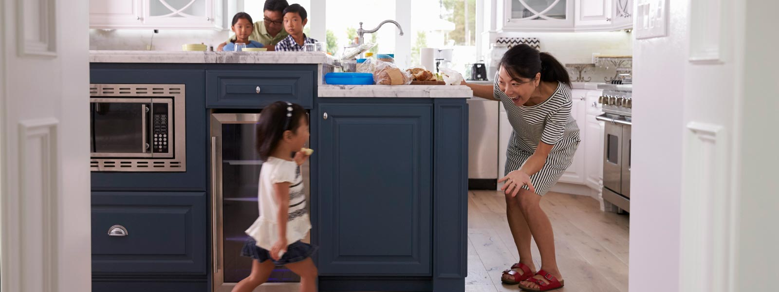 A mother playing with her daughter in a kitchen.
