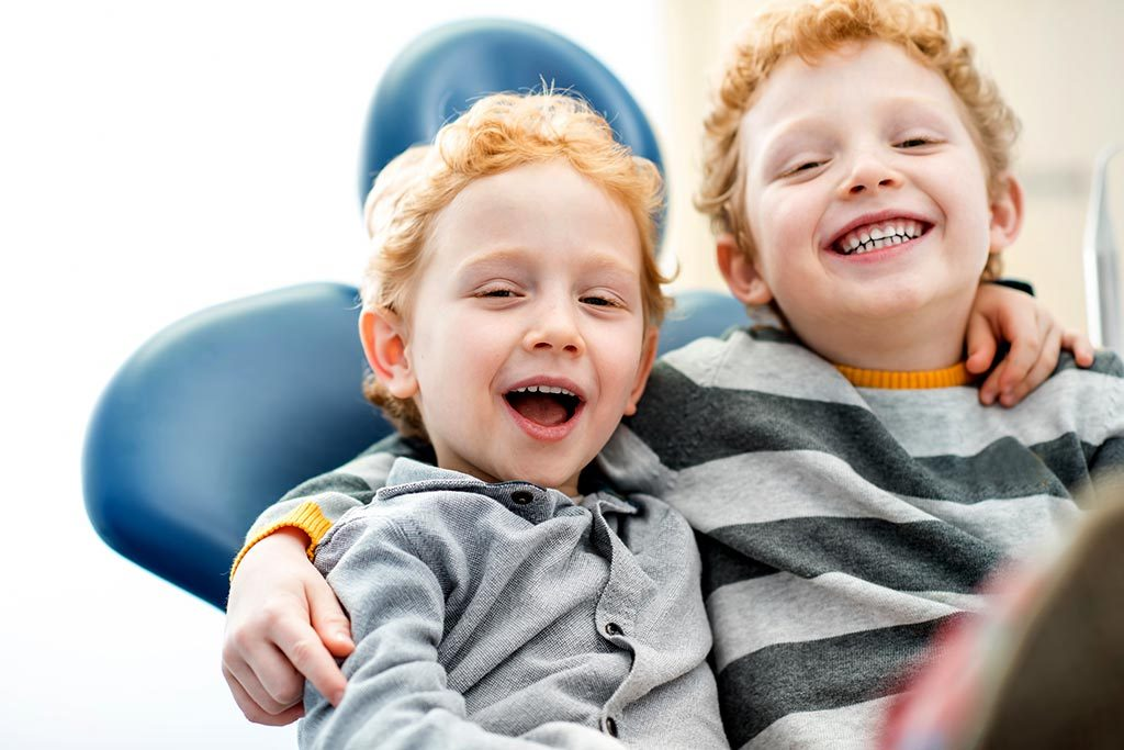 Two young boys smile while sitting in a dental chair.