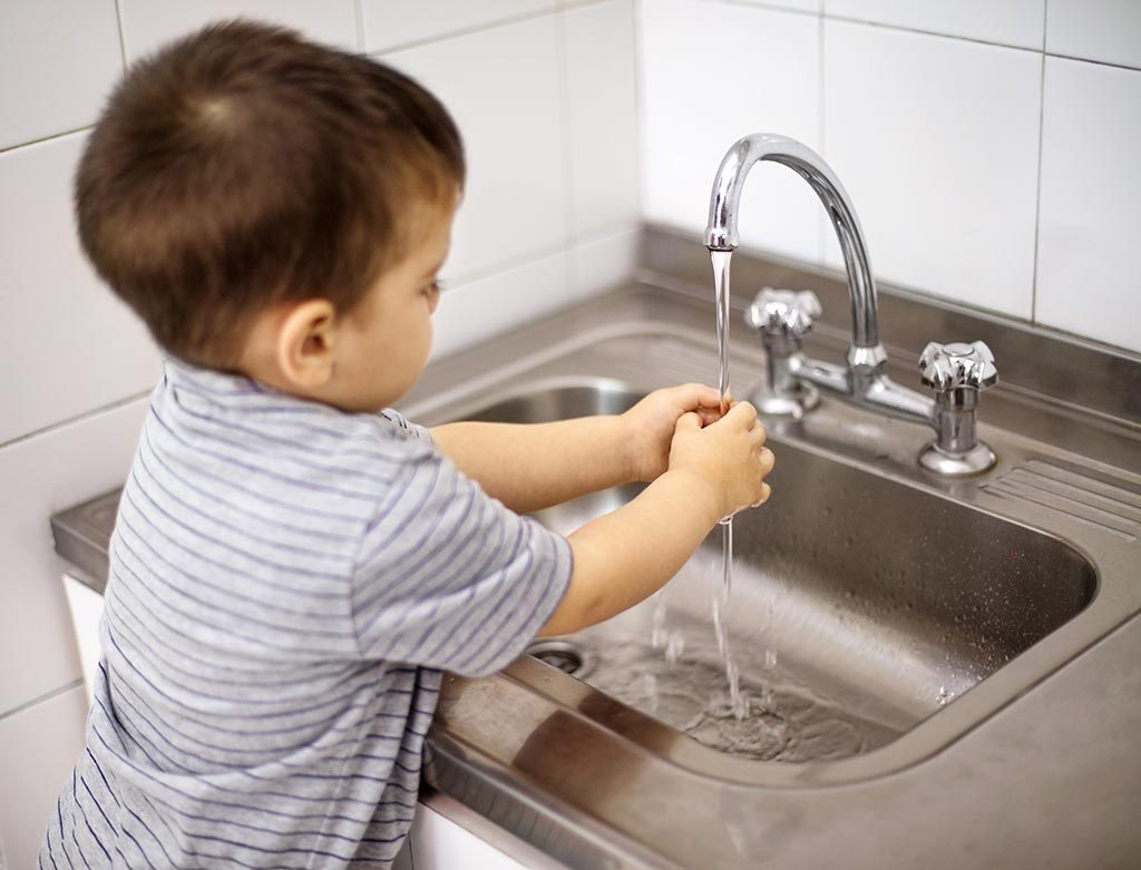 Toddler washing hands at daycare