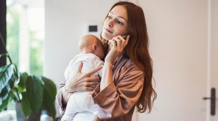 Mother holds baby while talking on phone.