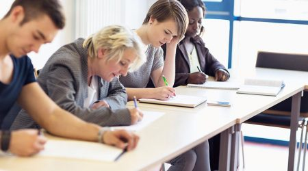 A group of people sitting at desks and writing an exam.