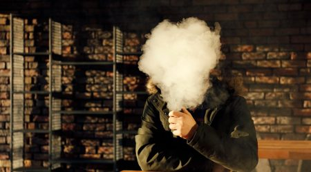 A person vaping with their face obscured by a cloud of vapor.