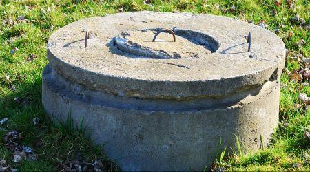 A dug well in a grass field.