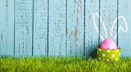 Pink Easter egg against a blue fence,
