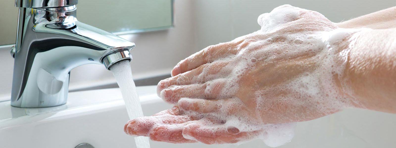 Washing hands in a bathroom sink.
