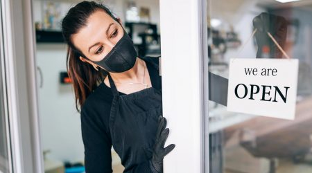Woman in mask turns over an open sign at a salon.