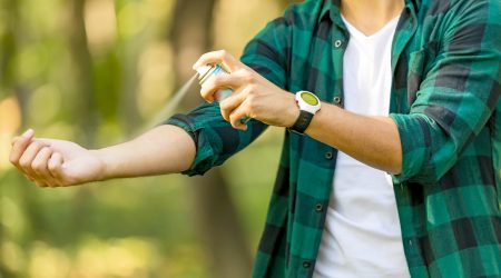 A young man sprays insect repellent on his arm.
