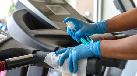 Disinfecting a treadmill at a gym.