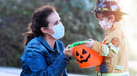 A mother and a child dressed as a fireman. Both are wearing masks due to COVID-19.