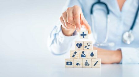 A doctor stacking blocks with medical symbols on them.