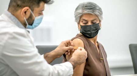 A doctor applies a bandage to an elderly woman's arm.