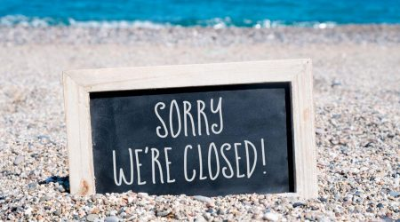 A closed sign in the sand on a beach.