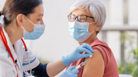 An elderly woman receives the COVID-19 vaccine.